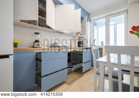 Details of cozy well designed teal-blue and white modern kitchen interior, some drawers are pulled out