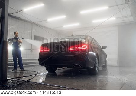 Man Spraying Water From High Pressure Washer To Wash A Car At Car Care Shop.