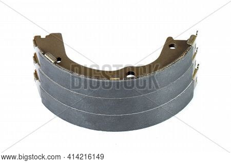 A Lot Of Brake Shoes For Drum Brakes, Spare Parts For Car Piled Up Brake Pads Isolated Objects On Wh