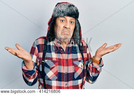 Handsome mature man wearing winter hat with ear flaps clueless and confused expression with arms and hands raised. doubt concept.