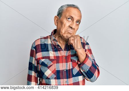Senior hispanic man wearing casual clothes thinking concentrated about doubt with finger on chin and looking up wondering