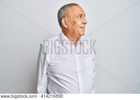 Handsome senior man wearing casual white shirt smiling looking to the side and staring away thinking.