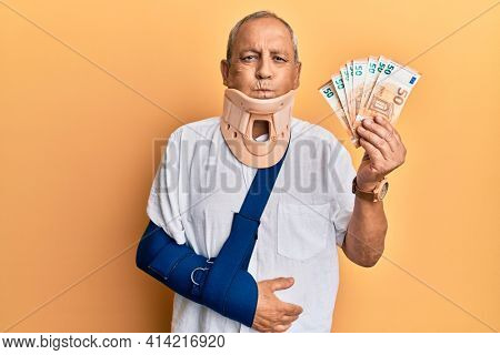 Handsome mature injured man wearing cervical collar and sling holding insurance euros puffing cheeks with funny face. mouth inflated with air, catching air.