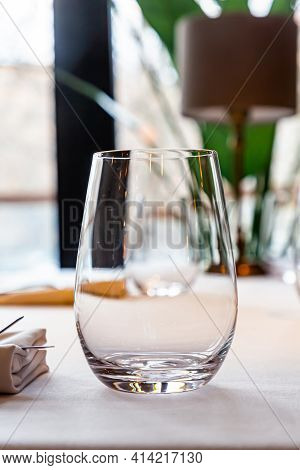 Empty Glasses And Cutlery Stand On The Table In The Restaurant Waiting For Guests. Serving Table