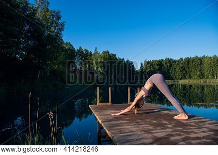 Beautiful Young Woman Performing A Spiritual Yoga Pose On A Forest Lake At Sunny Day, Sunrise Zen We