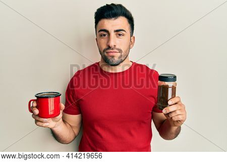 Young hispanic man holding cup of soluble coffee relaxed with serious expression on face. simple and natural looking at the camera.