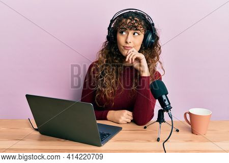 Young hispanic girl working at radio office thinking concentrated about doubt with finger on chin and looking up wondering