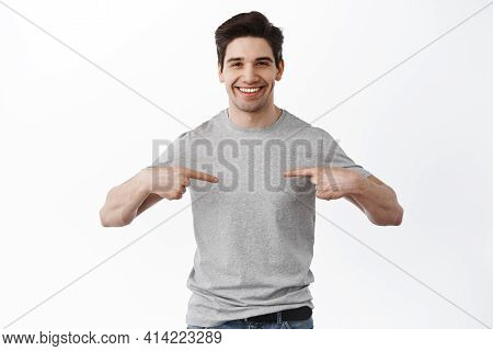 Cheerful Adult Man Smiling And Pointing At Center T-shirt Showing Your Logo, Pointing At Banner Comp