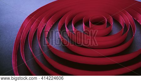 Maroon Satin Ribbon Laid In Circles In A Spiral On A Black Background. Abstract Background. An Endle
