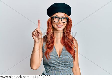 Young redhead woman wearing fashion french look with beret showing and pointing up with finger number one while smiling confident and happy.
