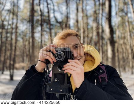 Young Man Photographing On Old Photo Camera In Forest. Handsome Guy Taking Photos With Old Camera In