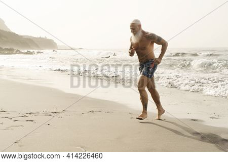 Happy Fit Senior Is Having Fun Bath And Run At Sunset Time . Sporty Bearded Man Training With Run On
