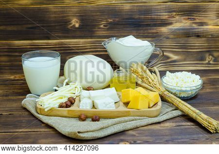 Set Of Dairy Products On A Wooden Background. Fresh Homemade Cottage Cheese, Yoghurt, Cheese, Kefir,