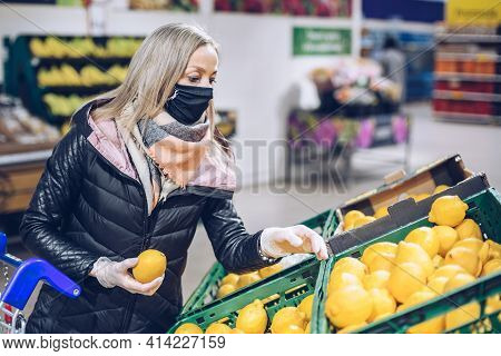 Woman In Face Mask Shopping For Fruits In Supermarket.