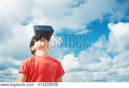 Child Standing In Nature In Virtual Reality Glasses. Boy Outdoors