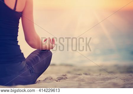 Young Woman Sitting On The Beach And Practicing Yoga