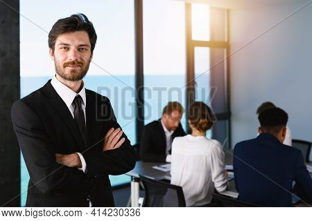 Confident Businessman In Office With His Teamwork. Concept Of Cooperation