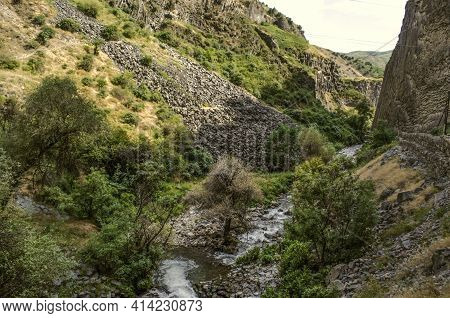 View Of The Basalt Slopes And The Azat River Flowing In Summer, Among The Bushes And Trees Along The