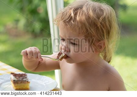 Baby Eating Cake. Cute Little Boy Eat Sweets. The Blond Boy Is Eating A Cake Outside. Hungry Kid Eat