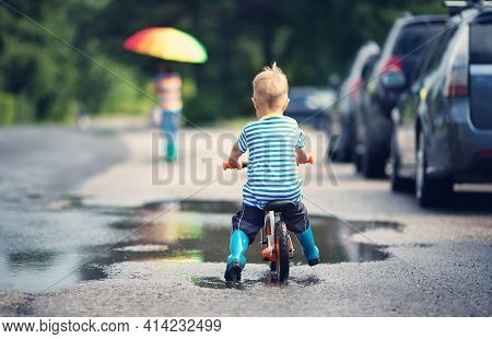 Child On A Balance Bicycle At Asphalt Road In Summer. Bike In The Park Moving Through Puddle On Rain