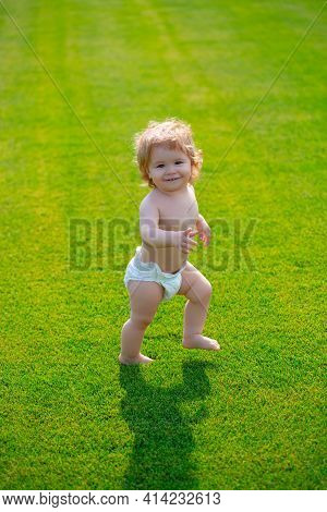 First Step. Baby Standing Barefoot On The Green Lawn In Diaper Pants. Beautiful Happy Little Boy Wal