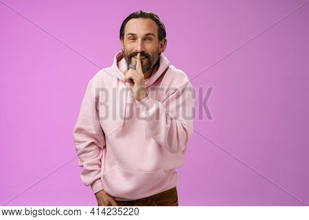 Lips Sealed Secret. Portrait Alluring Cheeky Stylish Adult Bearded Guy In Pink Hoodie Asking Keep Qu