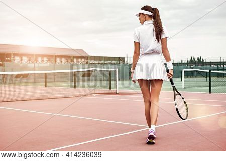Enjoying The Game. Beautiful Tennis Player With A Racket On A Court