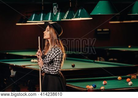 A Girl In A Hat In A Billiard Club With A Cue In Her Hands.pool Game