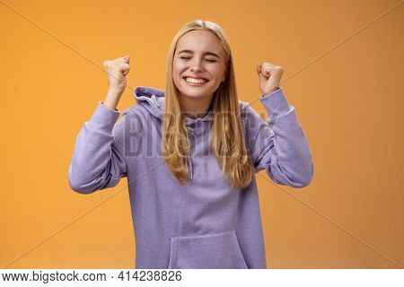 Triumphing Celebrating Positive Fair-haired Young Female Winner Raise Hands Clench Fists Up Victory