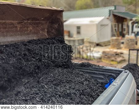 Front Loader Filling Pickup And Trailer With Black Mulch