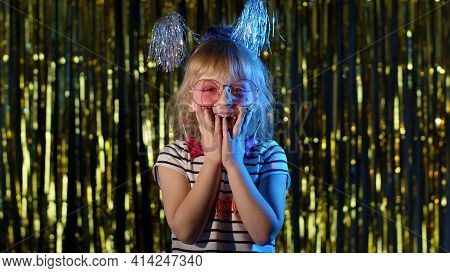 Trendy Girl In Stylish Pink Glasses Posing Raising Hands In Surprise Looking At Camera With Big Eyes