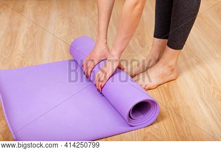 Equipment For Fitness, Pilates Or Yoga, Exercise Mat. Close Up Of A Womans Hands Is Rolling Up Exerc