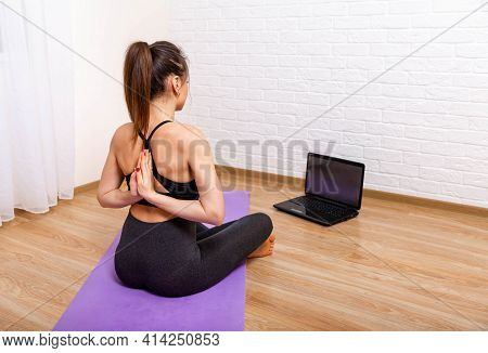 Beautiful Woman On Fitness Mat Training Online With Laptop While Quarantine. Young Attractive Woman