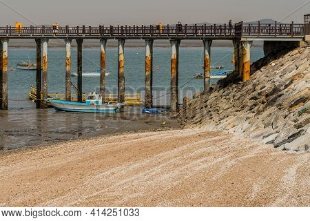 Pyeongtaek, South Korea; March 17, 2021: Small Fishing Trawler Moored To Pier Support Column At Low