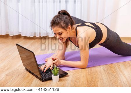 Attractive Young Woman Doing Yoga And Stretching Online At Home. Fit Woman Doing Yoga And Watching O