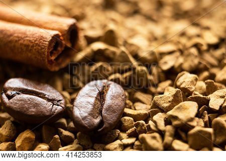 Beans Of Natural Roasted Coffee And A Cinnamon Stick Close-up Lie On The Granules Of Instant Coffee.