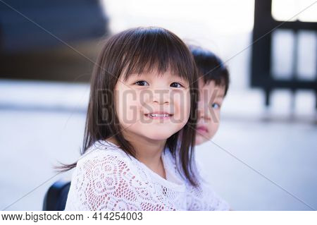 My Sister And Brother Play Together In Front Of The House. Cute Girl, Sweet Smile. Blur Boy Behind H