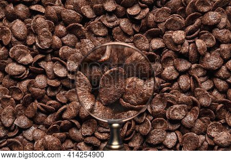 Chocolate Cereals Background. Breakfast Cornflakes With Cocoa, Close-up View Through A Magnifying Gl