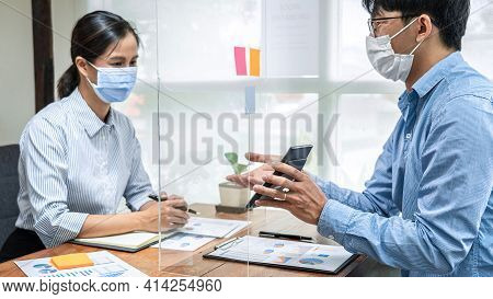Asian Business Man Showing Investment Amount On Calculator To Partner And Discussion About New Proje