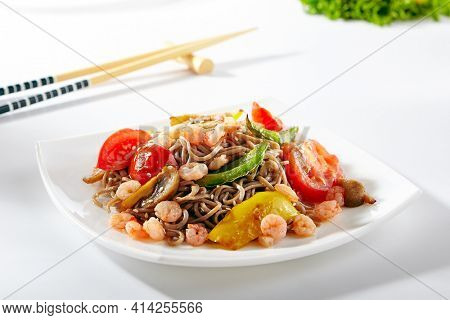 Soba noodles with seafood and vegetable. Asian style noodles food on white background. Soba in white plate with wooden choopsticks