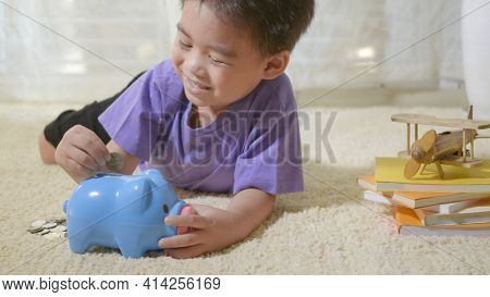 Happy Asian Kid Boy Preschool Putting Pin Money Coins Into Blue Faced Piglet Slot. Little Child Putt