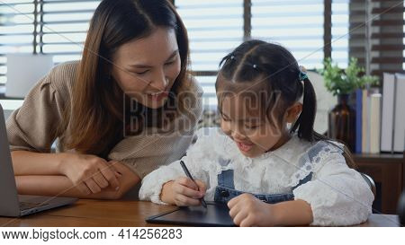 Asian Young Mother Working With Laptop Computer At Home And Help Daughter Doing Homework, Single Mom