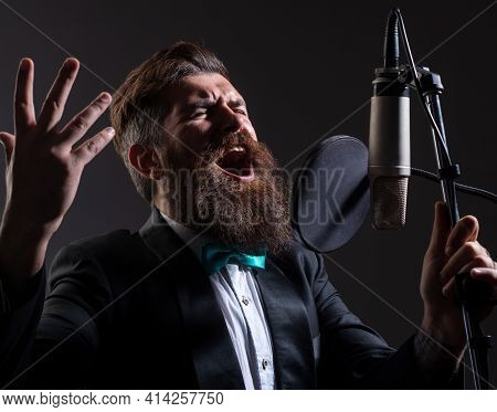 Classic Singer In Suit. Man With Microphone Singing Song. Musician In Music Hall. Funny Guy Singing