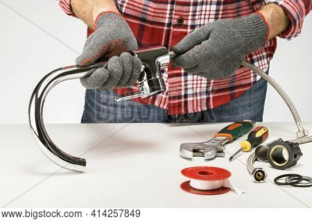 Plumber Muster Up Or Repairing Faucet On Kitchen Table. Do It Yourself Concept.