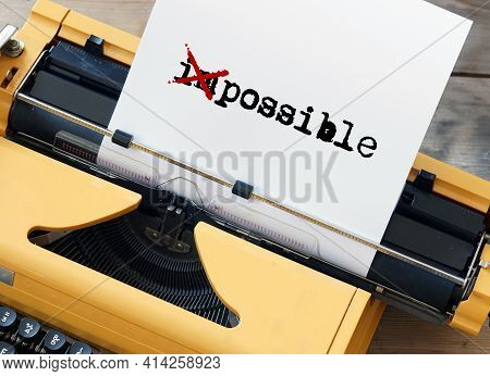 Possible Impossible - Word On Sheet Of Paper Written On Yellow Typewriter