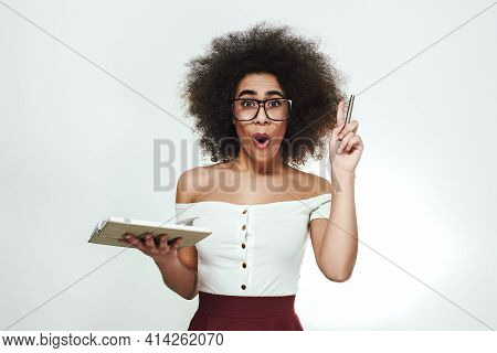 I Have A Great Idea Stusio Portrait Of Excitedd And Smart African Girl In Eyewear Holding A Notebook