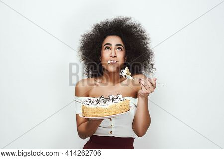 Yami Happy Young Afro American Woman With Curly Hair Is Eating Her Birthday Cake. Smiling And Lookin