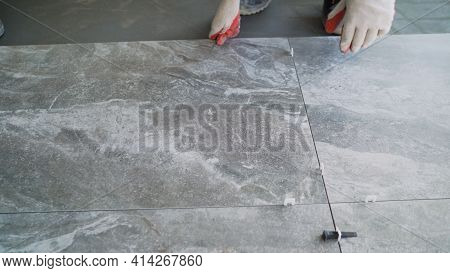 The Master Is Laying The Tiles On The Floor. Professional Worker Laying Tiles On Floor. Laying Floor