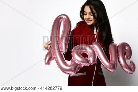 Portrait Of Smiling Caucasian Preteen Girl Model In Tracksuit Sportswear Holding Inflatable Word Lov