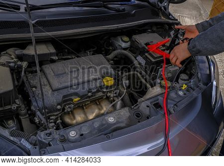 Mechanic Fixing Car On An Open Hood. Charging The Car Battery. Open Hood At Service Station Close-up